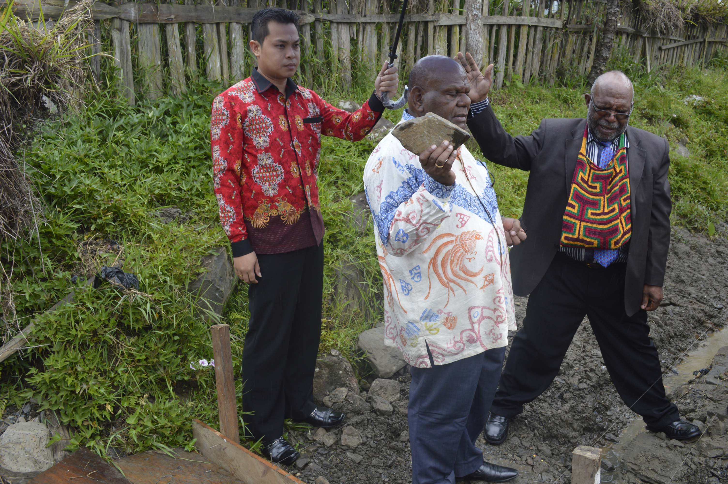 Drs. Henok Ibo saat meletakkan batu pembangunan Talud