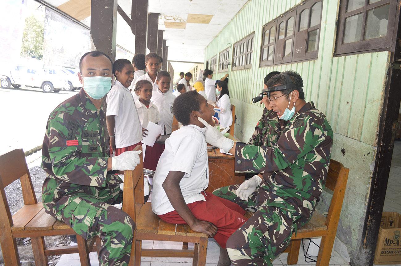 Salah Satu Dokter Dari TNI Tengah Memeriksa Siswa