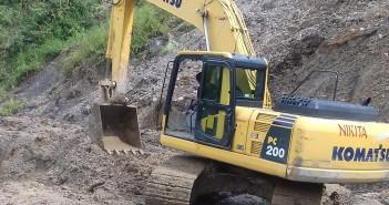 alat berat saat membersihkan tanah longsor dari badan jalan