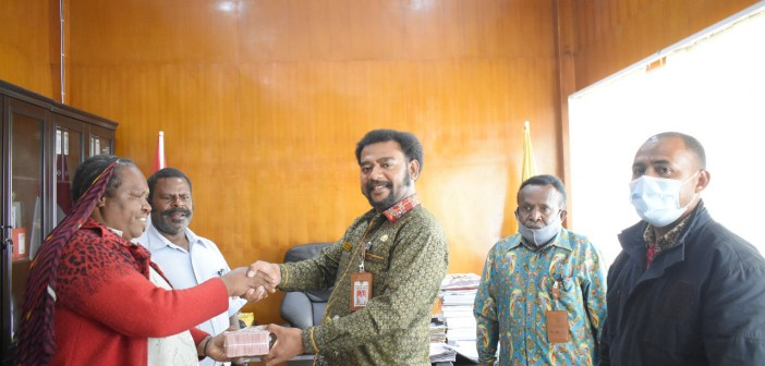 Asisten I Bid. Pemerintahan dan Kesra saat memberikan bantuan kepada Mama-Mama Papua GIDI